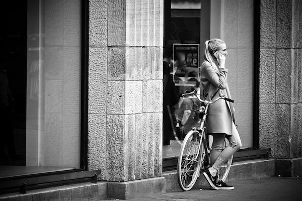 Una ragazza si ferma con la bicicletta per una telefonata: il giusto peso delle comunicazioni