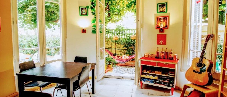 Particolare di camera Ostello con tavolo, chitarra, finestre e balcone con amaca